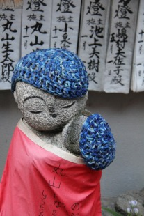 blue crochet caps on jizo in Kyoto temple